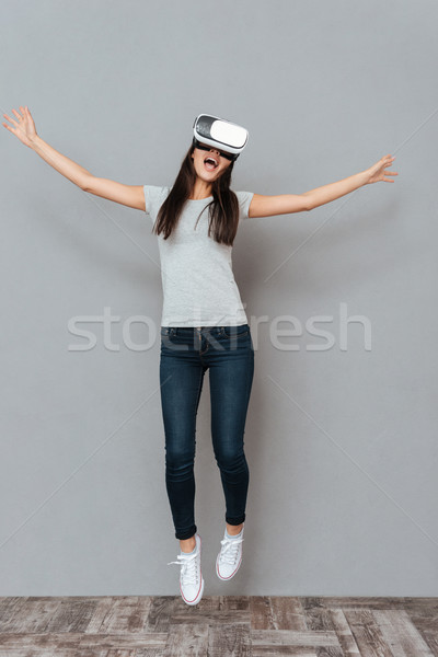 Happy woman in virtual reality glasses jumping and having fun Stock photo © deandrobot