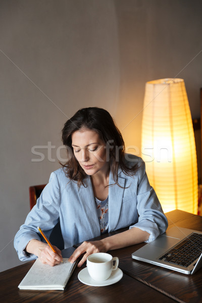 Thinking woman writer sitting indoors Stock photo © deandrobot