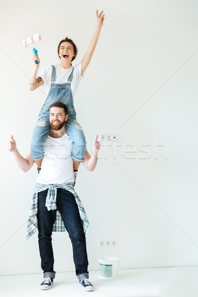 Happy cheerful couple renovating their house walls together Stock photo © deandrobot