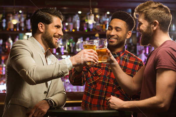 Happy smiling male friends clinking with beer mugs Stock photo © deandrobot