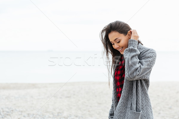 Positive woman looking down while walking on beach Stock photo © deandrobot