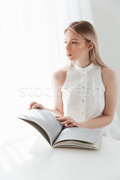 Concentrated blonde lady reading magazine. Stock photo © deandrobot