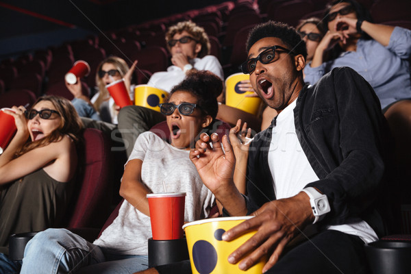 Scared young friends sitting in cinema watch film Stock photo © deandrobot