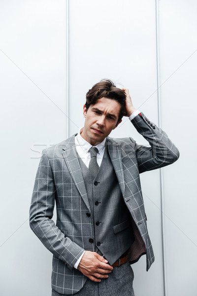 Thoughtful frowning man in suit standing Stock photo © deandrobot