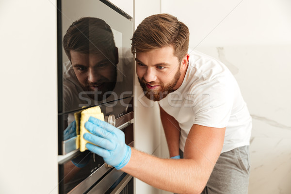 Side view of bearded man wipes a door of stove Stock photo © deandrobot