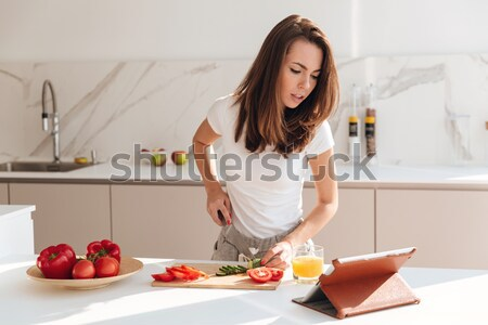 Smiling young woman cutting fruits on a wooden board Stock photo © deandrobot