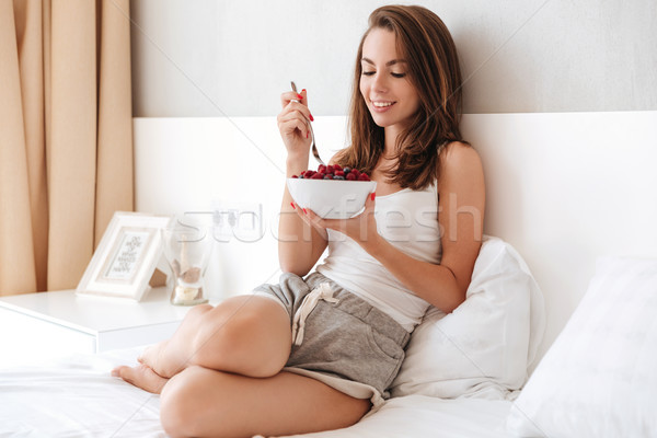 Smiling lovely woman eating fresh berries from a bowl Stock photo © deandrobot