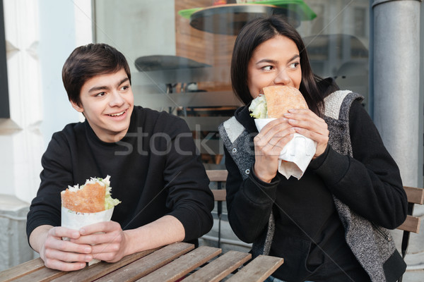 Brother and sister with burgers looking away Stock photo © deandrobot