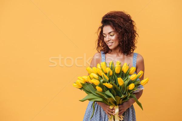 Mosolyog afrikai nő tart virágcsokor virágok Stock fotó © deandrobot