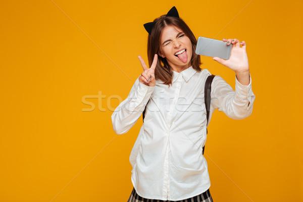 Crazy teenage schoolgirl in uniform with backpack Stock photo © deandrobot