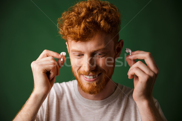 Handsome curly redhead man in white t-shirt insert earphones in  Stock photo © deandrobot