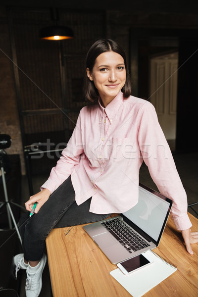 Vertical image of smiling brunette woman sitting on table Stock photo © deandrobot