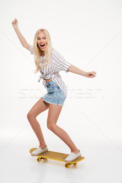 Full length portrait of a happy woman riding a skateboard Stock photo © deandrobot