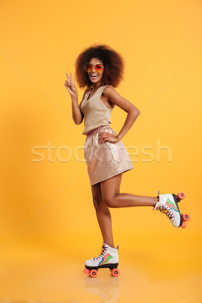 Full length portrait of a laughing afro american woman Stock photo © deandrobot