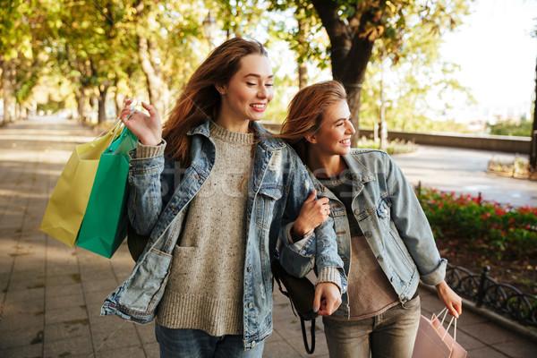 Portrait of two smiling joyful girls holding shopping bags Stock photo © deandrobot