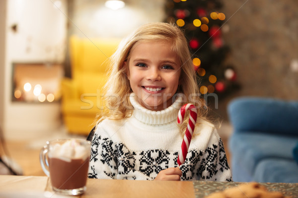 Smiling little girl holding candy cane, looking at camera while  Stock photo © deandrobot