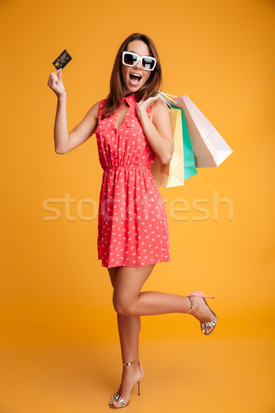 Full-length portrait of young happy woman in sunglasses holding  Stock photo © deandrobot