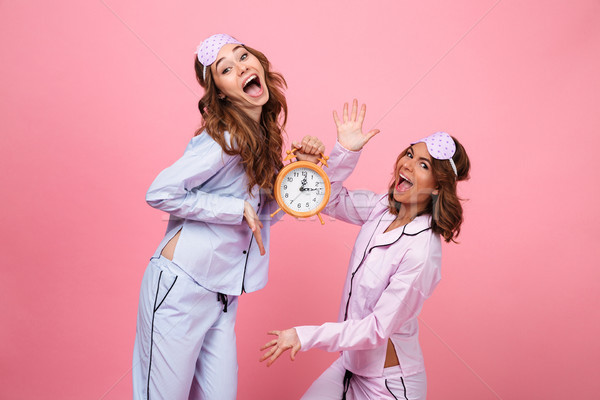 Funny emotional screaming friends women in pajamas holding alarm Stock photo © deandrobot
