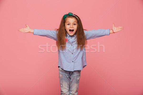 Cheerful little girl in hair hoop posing with open hands against Stock photo © deandrobot