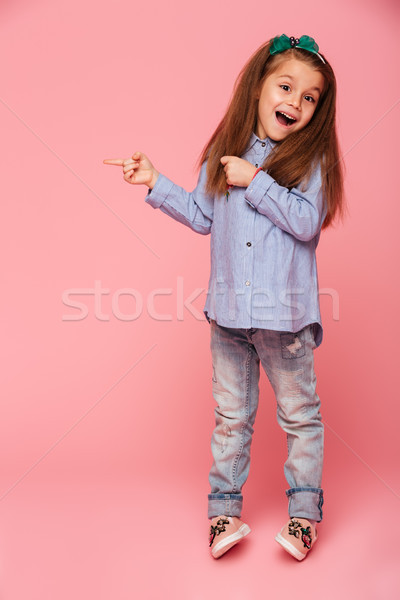 Full-length picture of funny little girl gesturing pointing inde Stock photo © deandrobot
