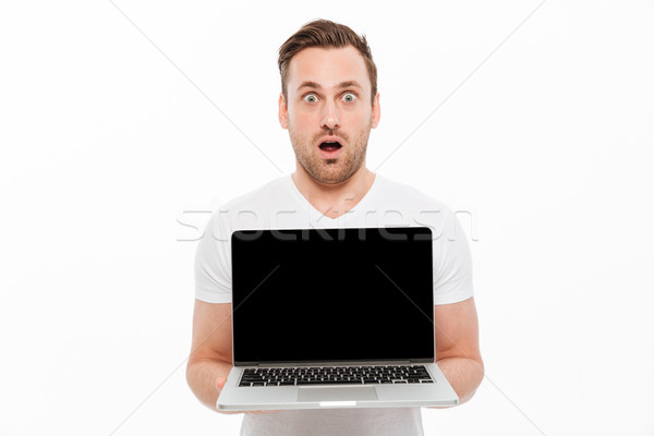 Shocked young man showing display of laptop. Stock photo © deandrobot