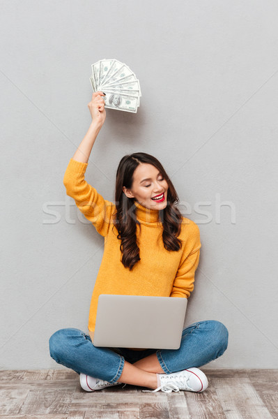 Vertical image of Pleased brunette woman sitting on the floor Stock photo © deandrobot