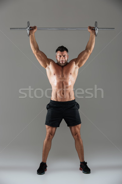 Full length portrait of a muscular serious shirtless male bodybuilder Stock photo © deandrobot