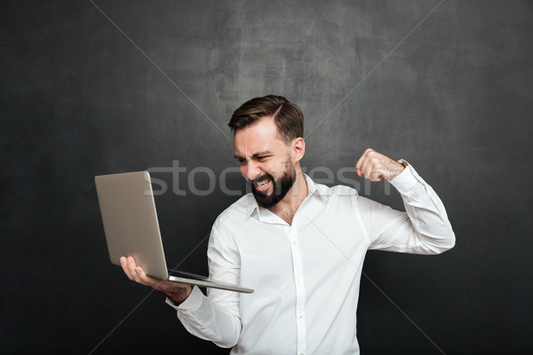 Portrait of agressive bearded man holding silver personal comput Stock photo © deandrobot