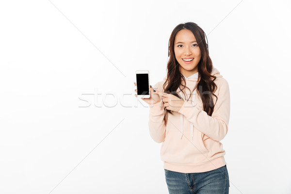 Asian happy woman showing display of mobile phone. Stock photo © deandrobot