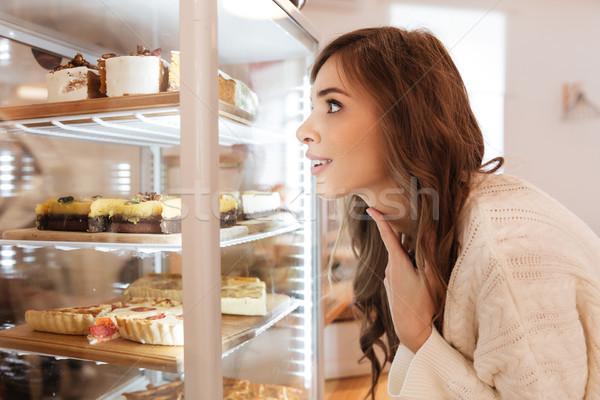 Közelkép boldog lány néz sütemény kirakat bent Stock fotó © deandrobot