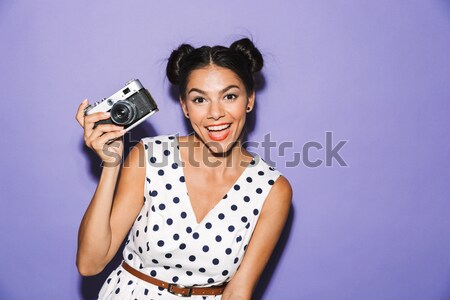 Portrait of a pretty cheery girl holding photo camera Stock photo © deandrobot