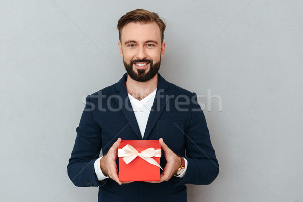 Smiling bearded man in business clothes holding gift Stock photo © deandrobot