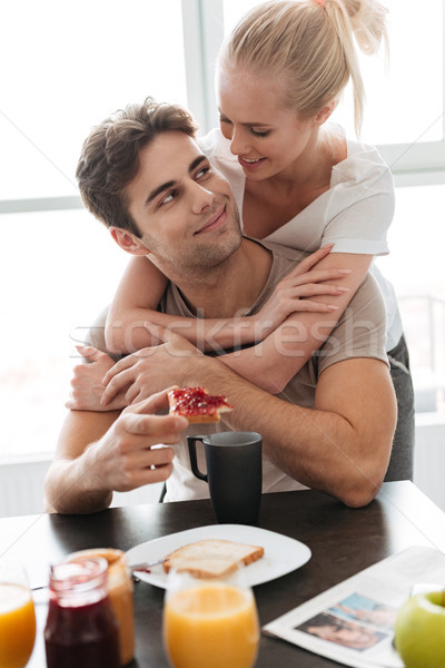 Young lady hug her man while they have breakfast Stock photo © deandrobot