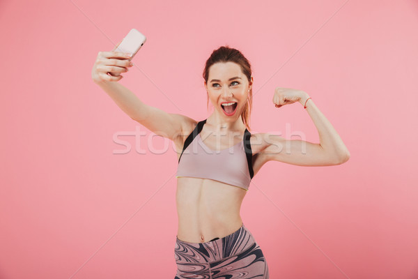 Happy sportswoman making selfie on smartphone while showing her bicep Stock photo © deandrobot