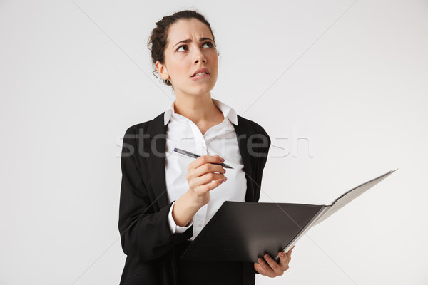 Portrait of a pensive young businesswoman taking notes Stock photo © deandrobot