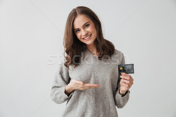Pleased brunette woman in sweater holding credit card Stock photo © deandrobot