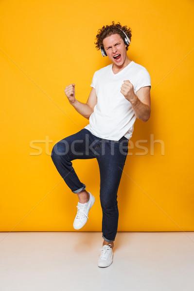 Fotografia młodych uśmiechnięty facet kręcone włosy Zdjęcia stock © deandrobot