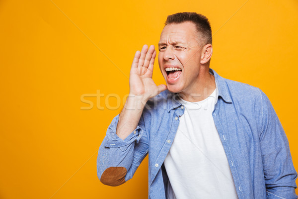 Portrait of a cheerful middle aged man shouting loud Stock photo © deandrobot