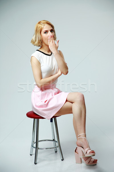 Young woman sitting on the chair and yawning on gray background Stock photo © deandrobot
