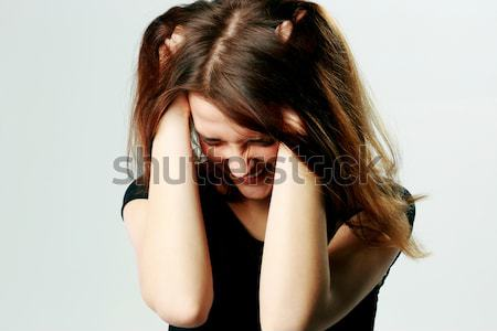 Portrait of a frustrated young screaming woman pulling her hair on gray background Stock photo © deandrobot