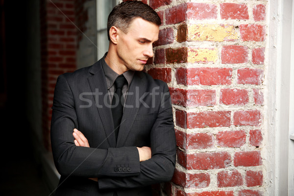 Pensive businessman standing with arms folded near brick wall Stock photo © deandrobot