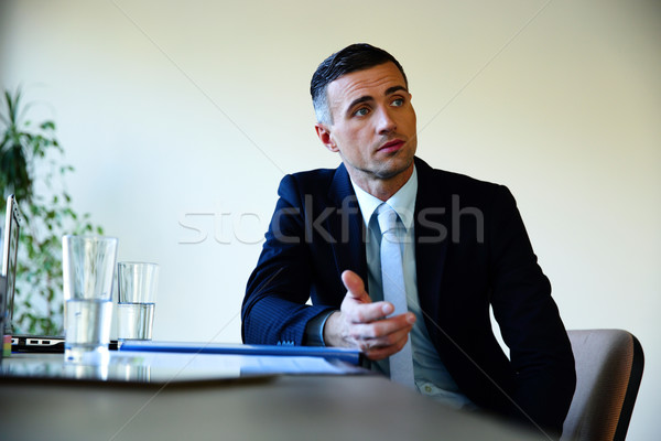 Businessman sitting at the table and explaining something Stock photo © deandrobot