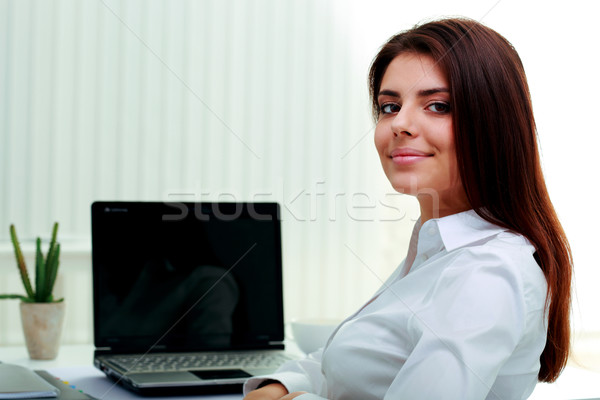 Stock photo: Happy young businesswoman sitting at the table on her workplace in office