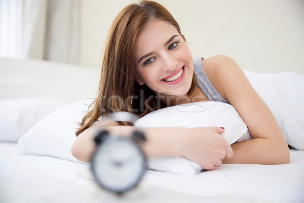 Pretty happy girl waking up in the morning and looking on alarm clock Stock photo © deandrobot