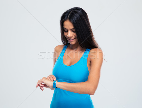 Happy sporty woman using fitness tracker Stock photo © deandrobot