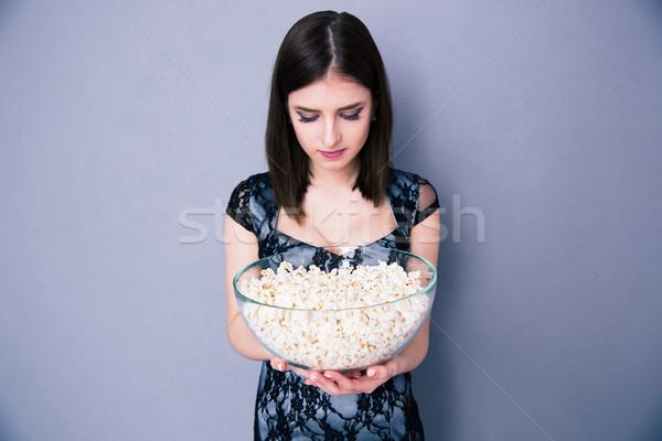 Fiatal nő tart tál pattogatott kukorica szürke nő Stock fotó © deandrobot