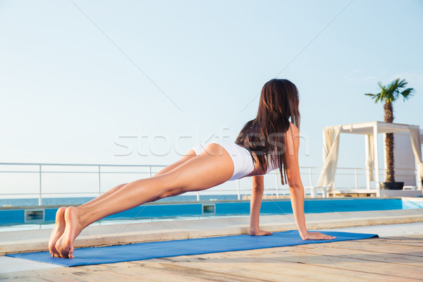 Girl making yoga exercises on yoga mat  Stock photo © deandrobot