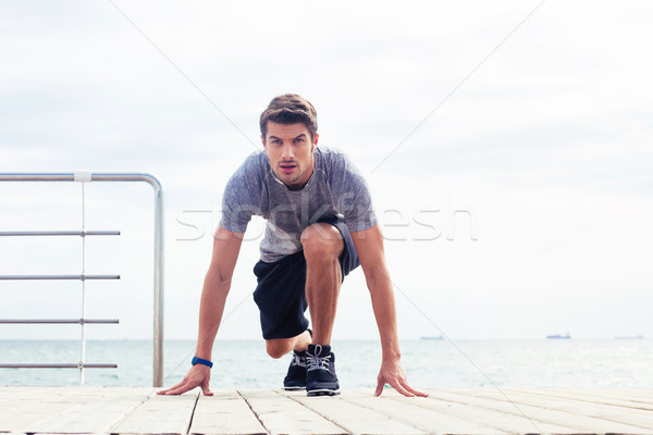 Runner standing in start position outdoors Stock photo © deandrobot