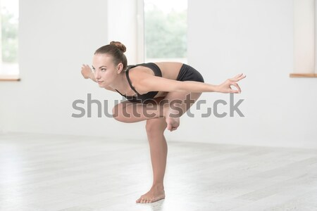 Attractive young girl doing acrobatic stunt Stock photo © deandrobot