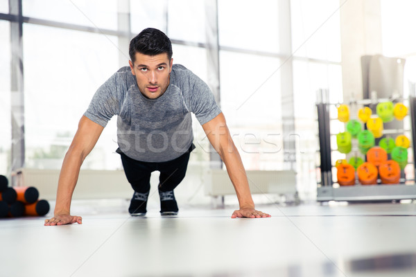 Stock photo: Man doing push-ups in gym